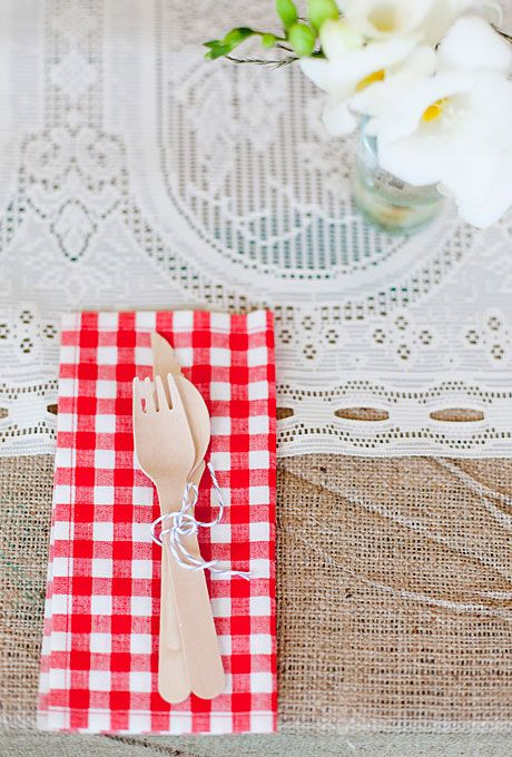 The bride purchased bamboo cutlery that she tied with grey and white twine and placed atop red gingham napkins.