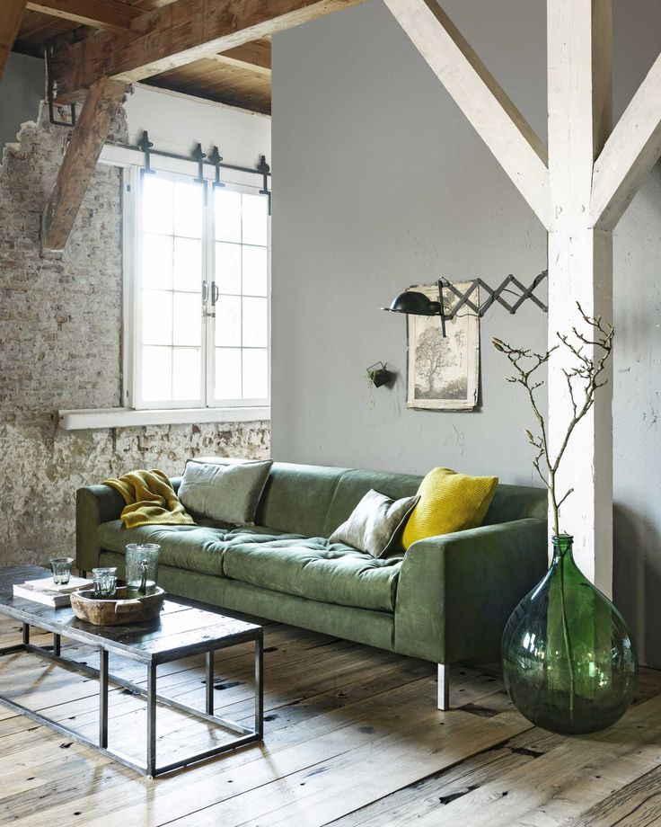 Rustic living room with exposed beams, exposed brick and a green sofa