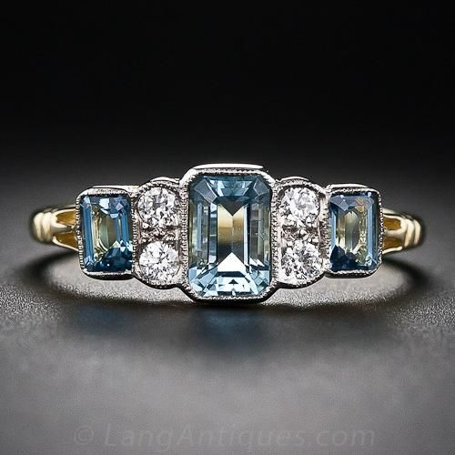 18K Aquamarine and Diamond Ring. A trio of bright and beautiful, deep pastel-blue emerald-cut aquamarines, together weighing 1.37 carats, alternate with pairs of bright-white sparkling diamonds in this sleek and stunning ring, crafted in London, England in homage to 1930s vintage Art Deco style. 18 karat two-tone gold, hallmarks inside ring shank.