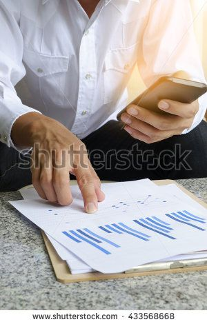 businessman holding mobile phone with analyzing financial chart on tablet , strategy concept