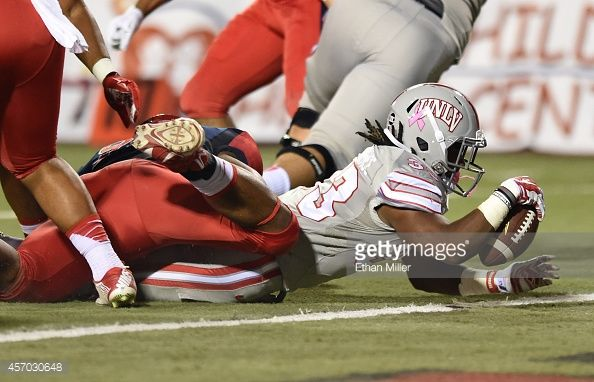 Shaquille MurrayLawrence of the UNLV Rebels breaks the plane of the goal line to score a touchdown as he is brought down by Todd Hunt of the Fresno...