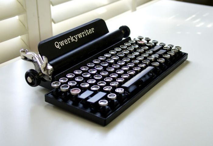 The Qwerkywriter is an 84 key, USB, mechanical keyboard that has been specifically designed to simulate a tactile feel of a vintage typewriter, and features custom typewriter inspired keycaps for an authentic look. The Qwerkywriter's tablet stand can accommodate a wide range of tablets up to 5/8 inches thick. | Geeky Gadgets