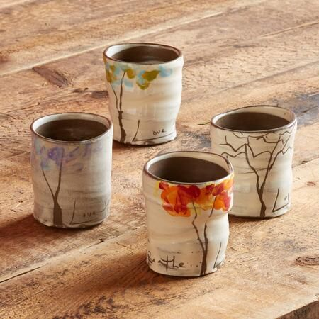 """FOUR SEASONS TREE CUPS - These beautiful, handmade cups depict trees in each of four seasons with hand-detailed painting and inscriptions like """"Love the Trees"""" and """"Breathe."""""""