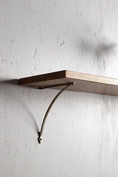 Simple bracket to hang shelves behind/above sofa w pictures, plants & personal items. Wishbone Bracket - anthropologie.com