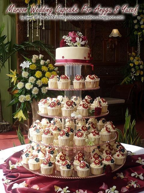 maroon wedding cake with cupcakes