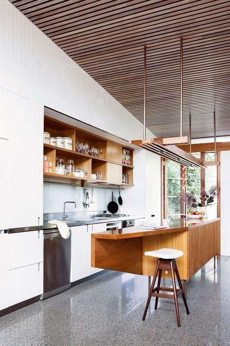 Kitchen: blackbutt timber ceiling battens, white cabinets with vertical panelling, glass splashback, grey polished concrete floor, timber linear pendant light, blackbutt island bench