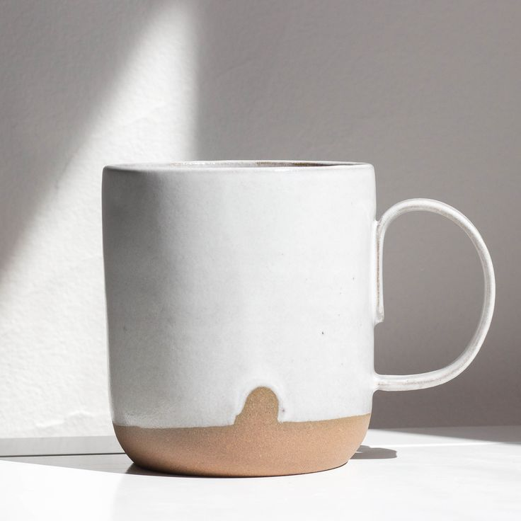 A beautiful wheel thrown mug from Wicked Wanda Pottery, white glaze inside and out with raw clay exposed ...