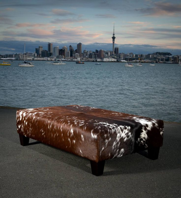 A large and beautiful cowhide ottoman coffee table with wooden legs. This is a very unique hide and the resulting ottoman was amazing. Cowhide furniture. We make these to order and each ottoman is unique. We can send our cowhide ottomans all over the world.
