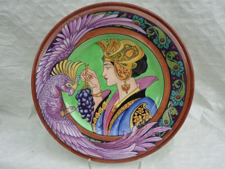 An exceptionally rare 1920s Burgess & Leigh (Burleigh Ware) wall plaque, designed by Charlotte Rhead in the 4111 pattern, having a tube-lined decoration of an ornately dressed lady in profile, holding a bunch of grapes in front a parrot, the wings of the bird forming part of the border decoration. It is highly probable that Charlotte herself completed the decoration of this plaque, given the intricacy and quality of the tube-lining.