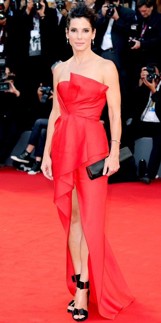 At the Venice Film Festival Gravity premiere Sandra Bullock one-upped everyone in a red-hot strapless silk J. Mendel gown with a high-low hem. She accessorized with Martin Katz jewelry and black Roger Vivier accessories.