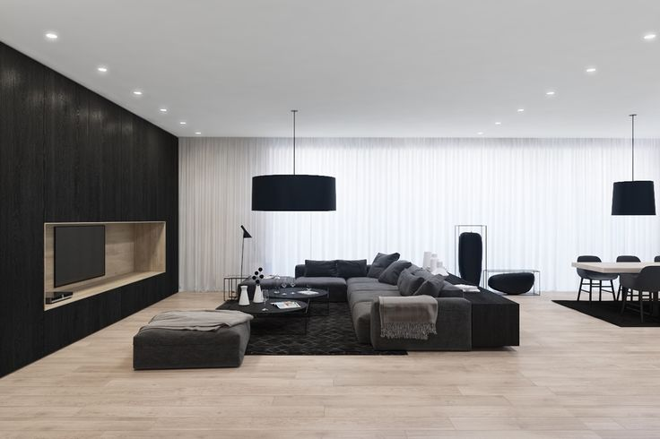 Bulgarian visualiser Velizar Dimitrov's apartment mingles black, white, and complementary tones in single surfaces. The living room feature wall combines light wood and black, while the rug beneath carries a white and grey stencil pattern, mimicked in the design of the accompanying tables.