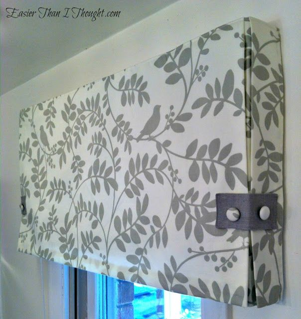 Box Pleat Valance - add button bands on the corners, and can also add a strip of the contrasting fabric to the bottom of the Roman shade that is underneath.  She attached the valence to the front of the 2 x 4 wood with a piece of velcro for easy installation and removal. Fabric is Botany Flora in Taupe by Robert Allen.