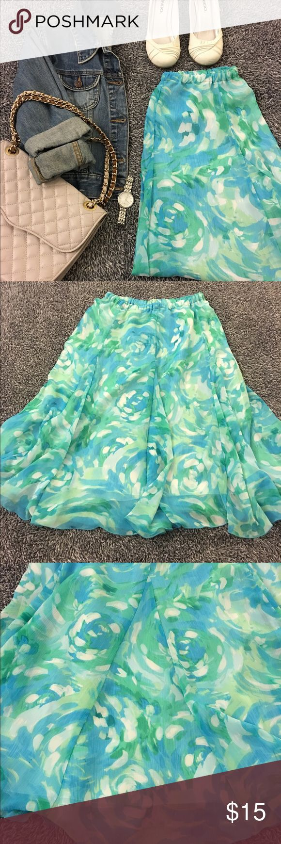Springy skirt - water colors & a-line style! Perfect feminine skirt with great style & flow. Soft & springy colors in blue/green tones. Elastic waist & mid length. Great shape. I didn't find any real flaws so if there are any they are not noticeable. Great shape & smoke free. See pics for details & condition! Would look good with light colored blazers or cardigans or a denim jacket. Waist is 13-18 in. flat with elastic. Hips are 18 with a line fit. Length is 27.5 inches. Has lining…