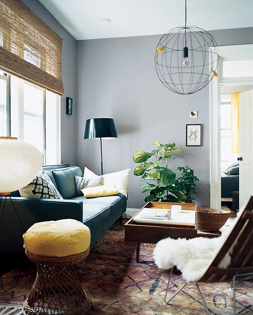 domino sitting or living room with teal sofa, wooden tray coffee table, gray walls and oriental rug. Grounded but fresh.