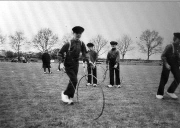 """Exloo. Festival Oude Ambachten. Jongens in klederdracht bezig met het spel """"hoepelen"""". Op de voorgrond Arjen Stevens. 1969-1979 Drents Archief #Drente"""