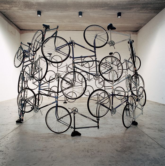 Bicycles by Ai Weiwei, 2003  Mori Art Museum, Tokyo  This sculpture was made from several dozen bicycles that were connected to each other at the wheel hinge by a simple seperation of the quick release lever that typically allows one to exchange or remove tires. Pretty interesting structure that somehow manages to balance using the seats as feet.