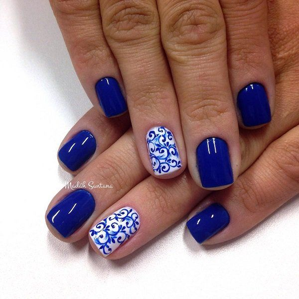 Intricate tribal themed nail art design. This design uses blue and white polish as base color. Beautiful tribal details intertwining with each other are then painted on top.