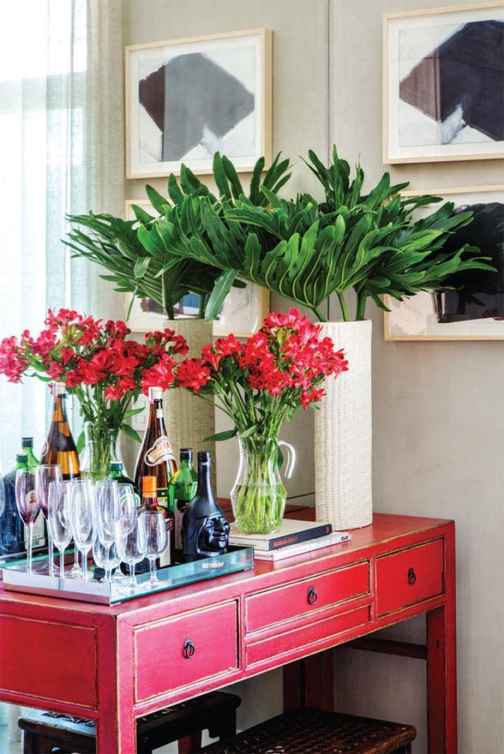 O aparador vermelho (Rug Hold) acomoda o bar, além de arranjos de fores frescas, dica de Paola para uma casa gostosa e convidativa.