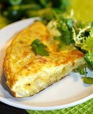 Klassieke Spaanse tortilla  Ingrediënten 1 rode ui 275 g vastkokende aardappelen 4 eetlepels olijfolie 1 teentje knoflook 20 g verse peterselie 5 grote eieren peper