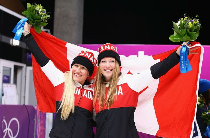 SOCHI, RUSSIA - FEBRUARY 19: Kaillie Humphries (L - Calgary, Alberta) and Heather Moyse (R - Summerside, Prince Edward Island) of Canada team 1 celebrate during the flower ceremony after winning the gold medal during the Women's Bobsleigh on Day 12 of the Sochi 2014 Winter Olympics at Sliding Center Sanki on February 19, 2014 in Sochi, Russia. (Photo by Al Bello/Getty Images)