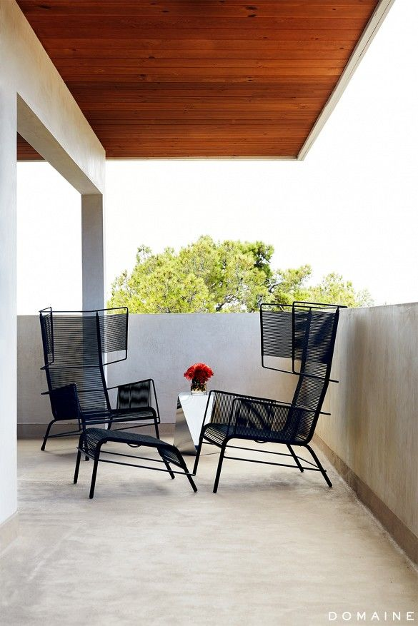 Modern outdoor balcony with wire wingback chairs.