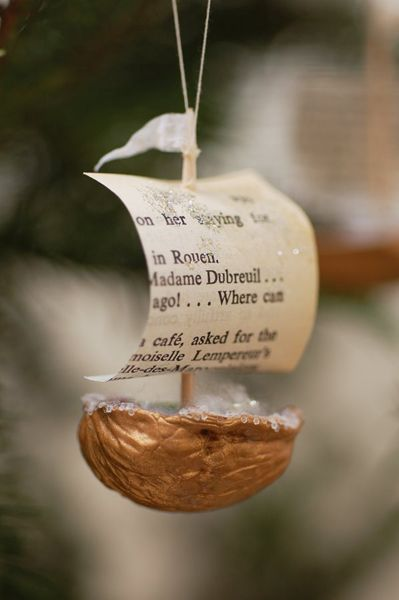 walnut boat ornament with book pages for sail (we made something similar for Columbus Day a long time ago with a salt-dough Italy and a blue poster of the world to sail them on)