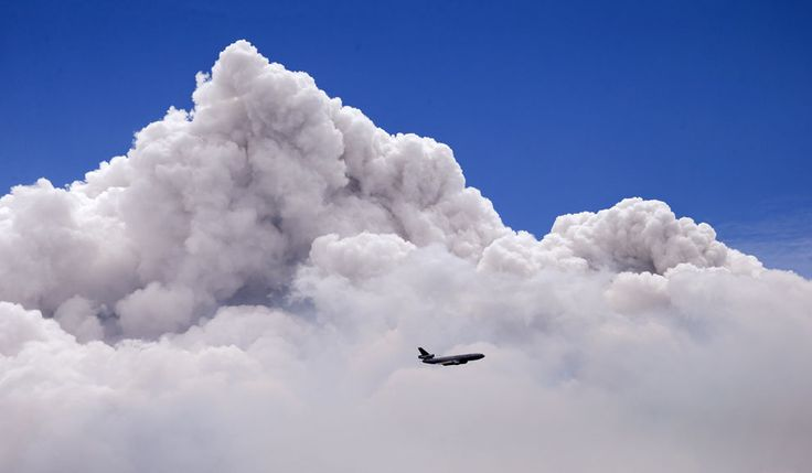 """""""A DC-10 air tanker is dwarfed by the tip of a rising smoke cloud as the plane prepares to drop fire retardant over a wildfire near Carlton, Washington, on July 19, 2014."""" (AP Photo/Elaine Thompson)"""