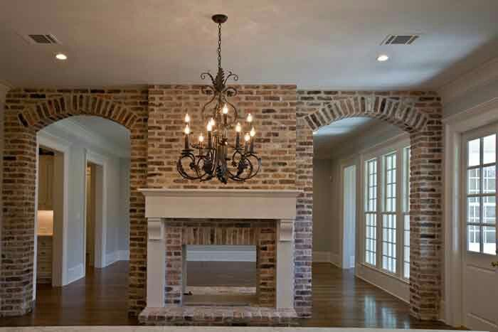 Arches on either side of the fireplace leading to the kitchen