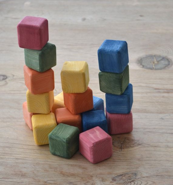 """These 1 3/8"""" cubes are finished with a water base wash. There are 18 cubes. They are designed to have fun and develop creativity and imagination in children. The blocks are soft, muted colors giving them a feel of times past. There is a cloth bag included making it easy to take them with you. These blocks are hand crafted so there are some irregularities. They are made from spruce."""