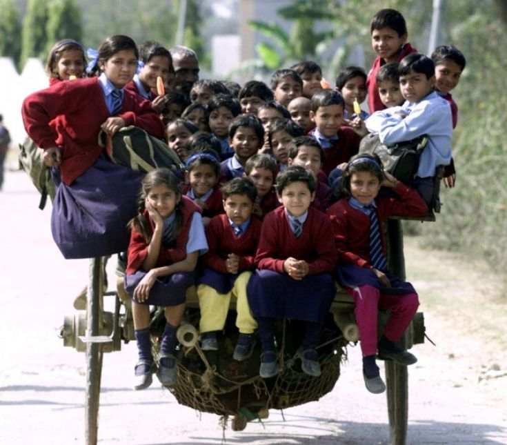 New Delhi, India. Oltre 35 bambini in divisa scolastica ammassati su un carretto trainato da un cavallo