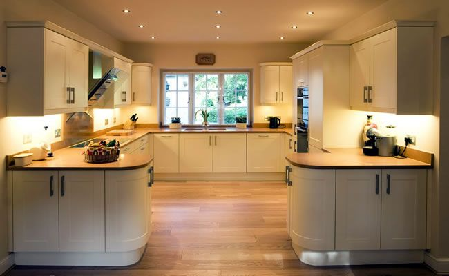 View of c-shaped kitchen with window on far back wall, and symmetrical layout to right and left. Furniture in Virginia Cream finish. Sonora Gold Silestone worktops throughout in a warm terracotta colour, and oak plank flooring.