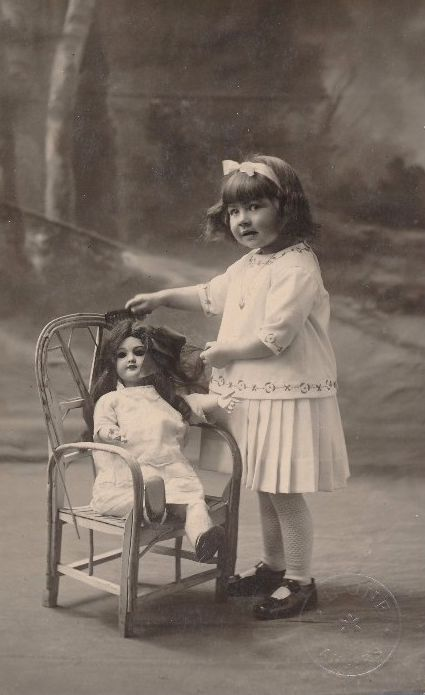 Vintage photo... Girl brushing her doll's hair. Early 1900s.