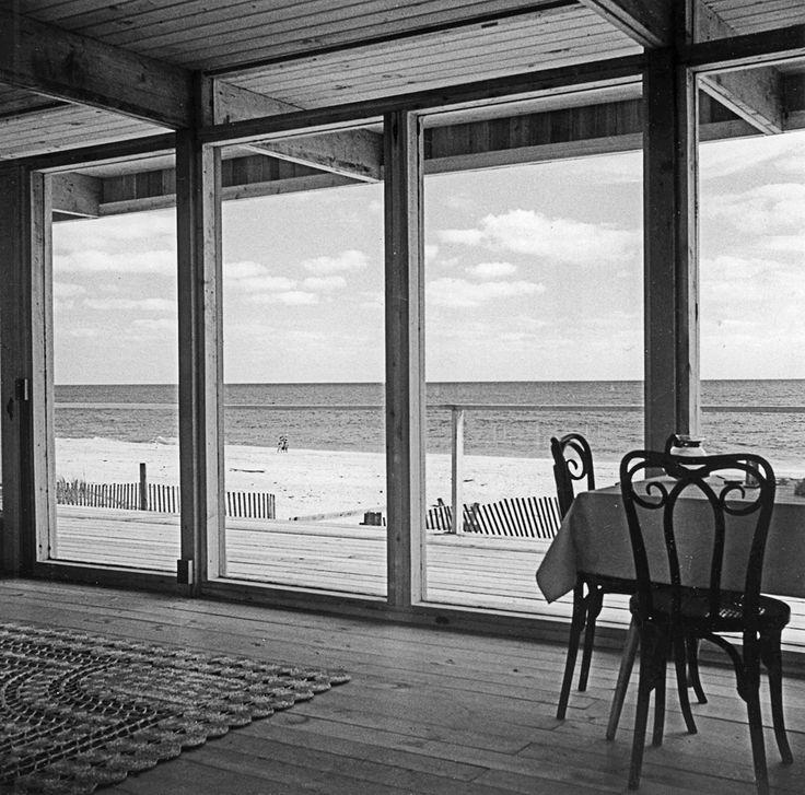 Жилая комната с остекленной стеной и видом на океан.  (гостиная,дизайн гостиной,интерьер гостиной,мебель для гостиной,столовая,дизайн столовой,интерьер столовой,мебель для столовой,балкон,лоджия,дизайн лоджии,дизайн балкона,ремонт балкона,ремонт лоджии,1950-70е,середина 20-го века,медисенчери,медисенчери модерн,архитектура,дизайн,экстерьер,интерьер,дизайн интерьера,мебель,mcm,средневековый модерн, модернизм, модерн) .