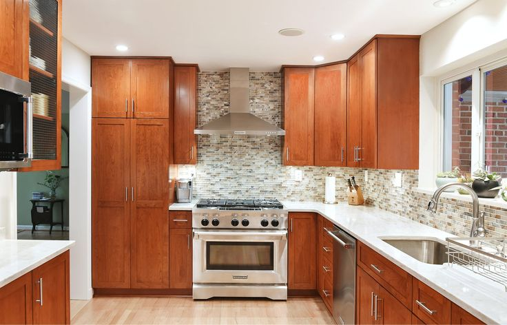 This Kensington, MD was refaced with cherry wood and enriched with new conveniences including a lazy susan, wine rack, tip out tray and trash can pullout. The shaker style doors blend contemporary style with the warmth of cherry. The clean lines of the design, tiles and hardware highlight the color and grain of the cherry cabinet doors. See more at https://www.kitchensaver.com/kitchen/kensington-md/