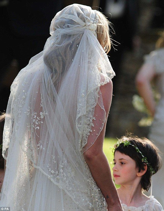 Kate's hair was styled in loose waves underneath the 1920s-style cap veil with flower embroidery on the lace
