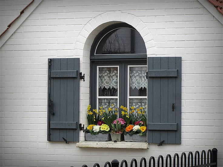 Pretty gray shuttered window in Valenciennes, white lace curtains and spring flowers give it a fresh, neat touch
