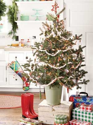 Holiday time usually means more time—and more people—in the kitchen cooking and baking. A small tree introduces Christmas spirit without getting in the way. Green hobnail glass and kitchen utensils from the '40s and '50s inspired the mint green and cherry red palette of this tree. Hang utensils amid homespun touches such as popcorn garlands and crisp gingham ribbon.   - CountryLiving.com