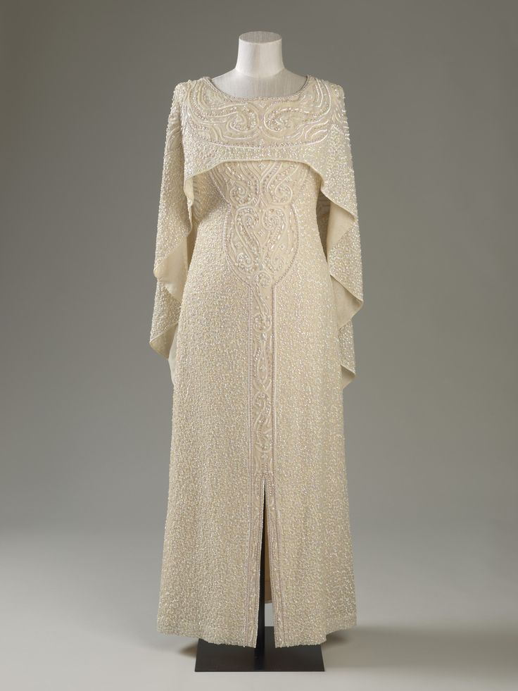 Worn for a Commonwealth Heads of Government Meeting at Buckingham Palace, 1977. This evening dress features a separate cape which sits over the sleeveless shift, covering the shoulders and bodice and falls into two panels with triangular tips at the back. The cream-coloured silk chiffon is enhanced by embroidery over the entire surface in multi-coloured iridescent sequins.