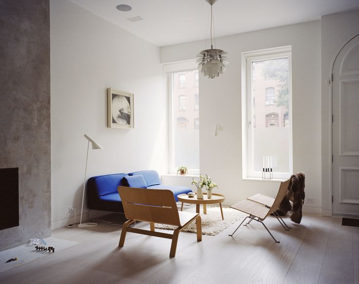 The living room is furnished with rattan chairs from Fritz Hansen, a Muuto side…