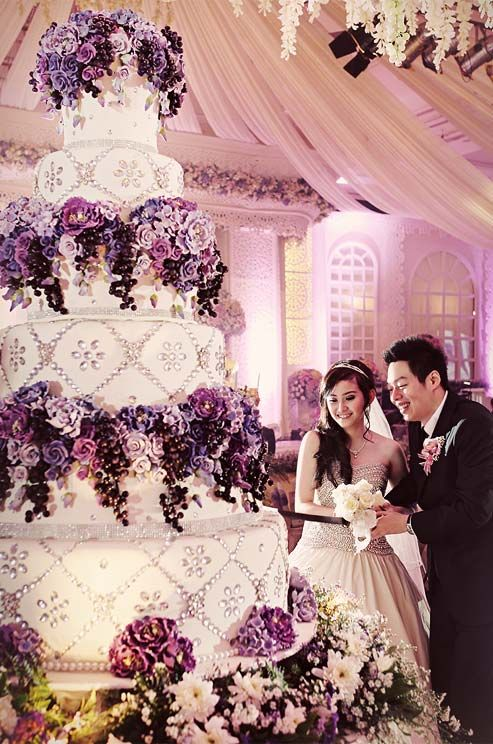 "At first glance, guests will be struck by just how tall and multi-layered this confection is. But there's a reason behind this combination: it is supposed to convey the hope for the couple as they ""climb"" the ladder to a successful marriage."