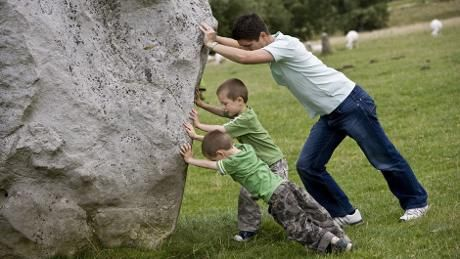 Family having fun pretending to push one of the ancient stones of the circle at Avebury, Wiltshire
