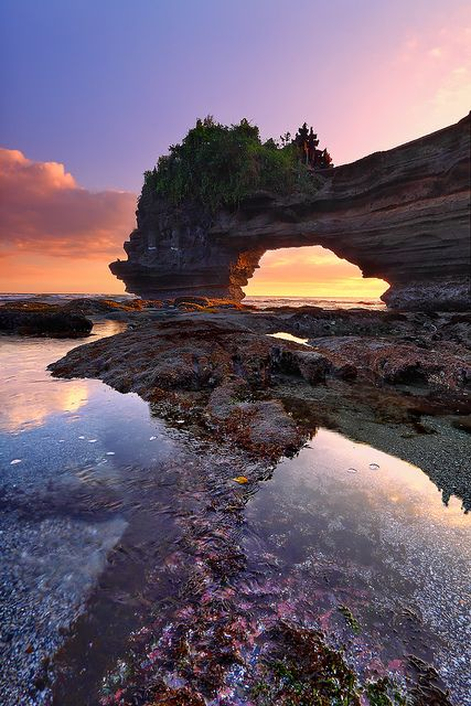 Pura Batu Bolong -Tanah Lot, Bali, Indonesia. Pura Batu Bolong is a small shrine located just a stone's throw from the famous Tanah Lot temple. It is perched at the end of a rocky promontory that leaps seaward into the surging Indian Ocean. Lombok Island Bali.