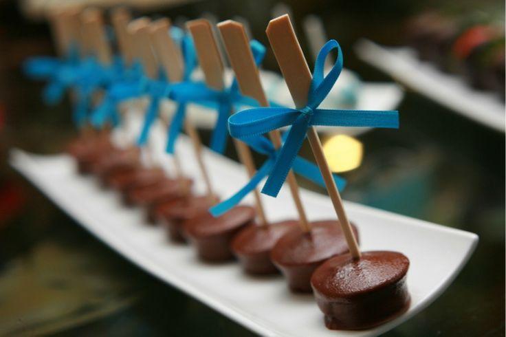 Elegantes malvaviscos cubiertos de chocolate con un pequeño palito y cinta se verán lindísimos.