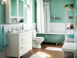 Lyst grønt, blått og hvitt bad med tradisjonelt badekar og skap med dobbelt servant.