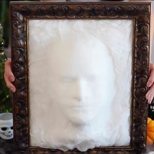 Make a single or a set of eerie ghost heads coming out of a frame. The technique is simple -- just cover a form head with cheesecloth and spray the layers with starch.