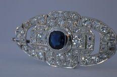 Platina art deco stijl diamanten broche bezaaid met diamanten en centraal een natuurlijke saffier