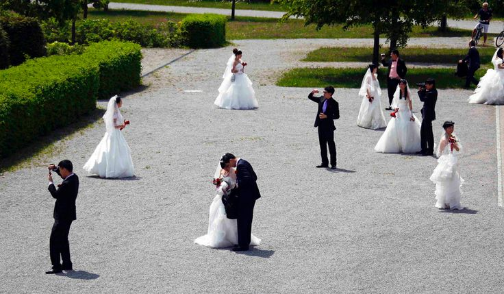 Chinese bridal couples take pictures after their symbolic wedding in Fuessen on May 31. The 15 Chinese couples who already got married in China, travelled to Germany to repeat their promise of marriage at Neuschwanstein Castle, one of the most popular destinations in Europe. (Michael Dalder/Reuters) #