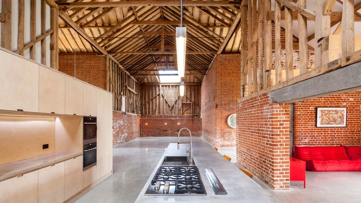 The original brick walls and high timber-trussed ceiling are left exposed inside this former barn in Suffolk, converted by David Nossiter Architects.