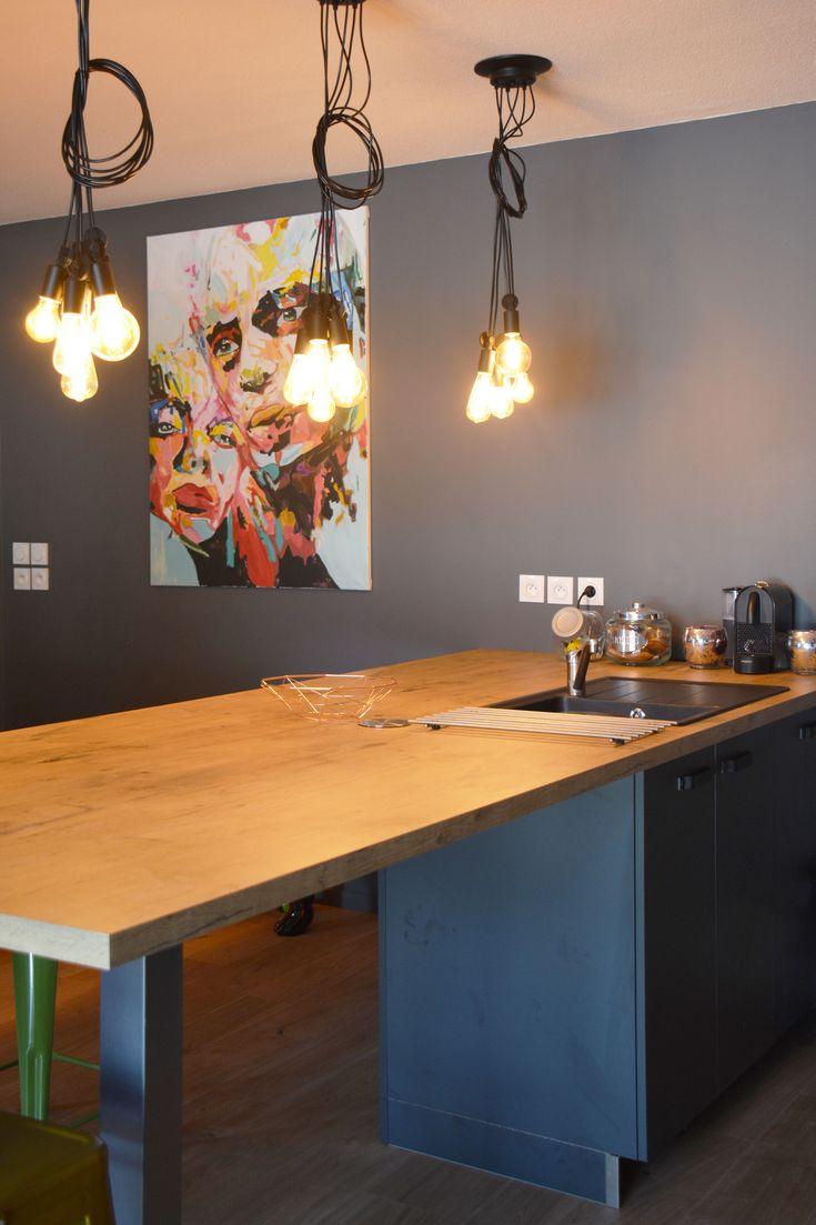 Grand plan de travail en bois pour la cuisine où il sert aussi de bar et de table de repas pour tous les jours. Des ampoules suspendues en filament pendent de manière aléatoire avec une jolie toile en fond !