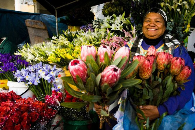 A flower seller poses with flowers at  the Adderley Street Flower Market in the Cape Town CBD